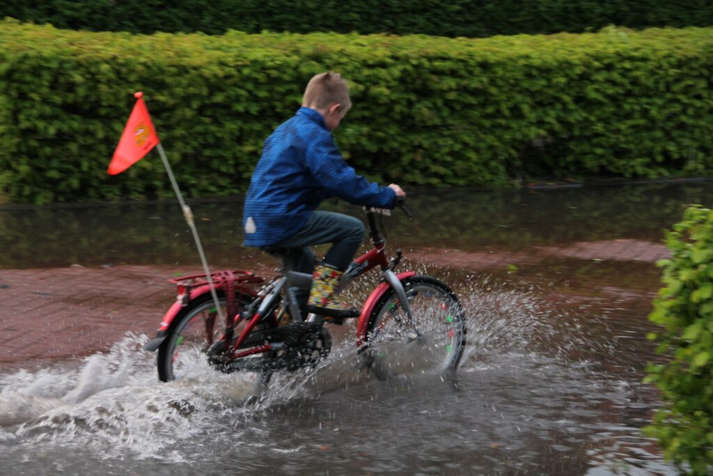 Dreng cykler igennem en vandpyt